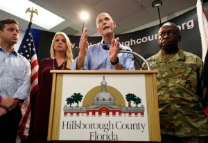 Gov. Rick Scott speaks accompanied by Florida Attorney General Pam Bondi, Lt. Gov. Carlos Lopez-Cantera, left, and Maj. General Michael Calhoun, right, during a news conference at the Hillsborough County Emergency Operations Center in Tampa, Fla. on Friday, Aug. 28, 2015. The governor and several local officials were on hand at the county E.O.C. to discuss Tropical Storm Erika and its possible impact on the state. (Chris Urso/The Tampa Tribune via AP)  ST. PETERSBURG OUT; LAKELAND OUT; BRADENTON OUT; MAGS OUT; LOCAL TELEVISION OUT; WTSP CH 10 OUT; WFTS CH 28 OUT; WTVT CH 13 OUT; BAYNEWS 9 OUT; THE TAMPA BAY TIMES OUT; LAKELAND LEDGER OUT; BRADENTON HERALD OUT; SARASOTA HERALD-TRIBUNE OUT; WINTER HAVEN NEWS CHIEF OUT; MANDATORY CREDIT